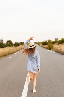道路の真ん中で走っている帽子をかぶった女性の背面図