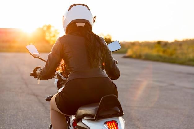 彼女のバイクに乗ってヘルメットを持つ女性の背面図