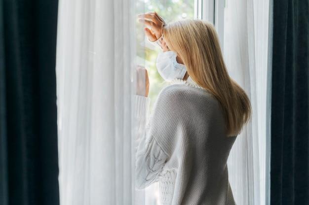 Вид сзади женщины с медицинской маской дома во время пандемии, смотрящей в окно