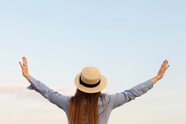 Вид сзади женщины с позированием на открытом воздухе с открытыми руками