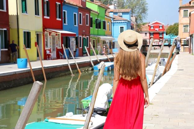 이탈리아 부라노 베니스에서 화창한 날 채널을 따라 걷고 있는 빨간 드레스와 모자를 쓴 여성의 뒷모습