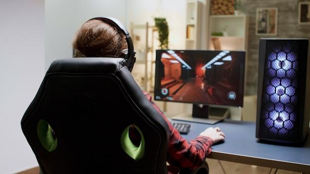 ゲーミングチェアに座ってオンラインシューティングゲームをプレイしている赤い髪の女性の背面図。
