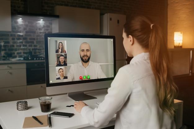 自宅のデスクトップコンピューターでビデオ会議でのビジネスについてリモートで同僚に話している女性の背面図。