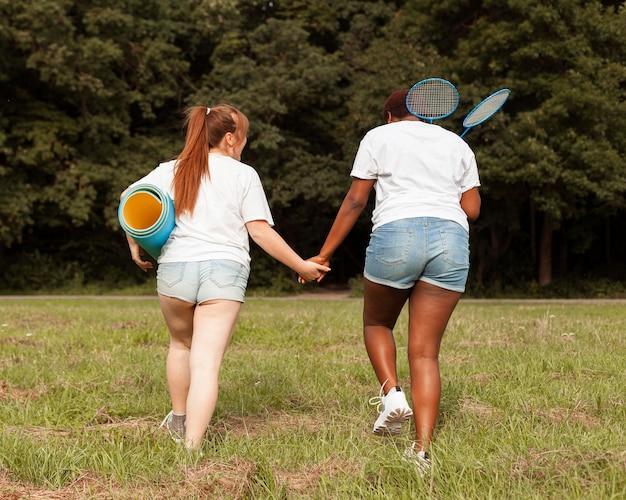 Вид сзади женщин, взявшись за руки на открытом воздухе
