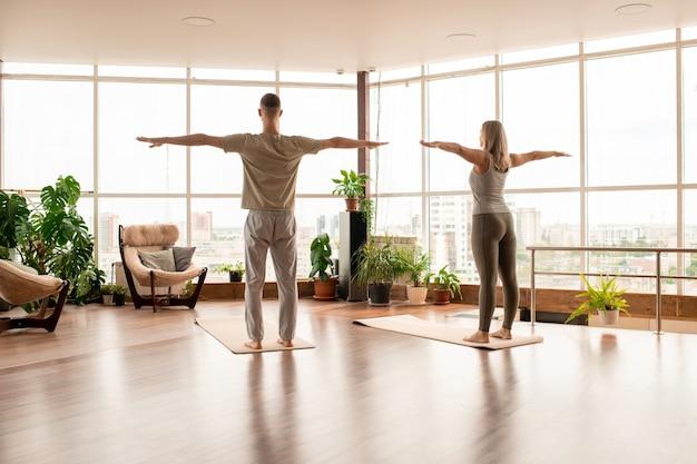 Вид сзади молодой активной пары в спортивной одежде, стоящей на циновках с вытянутыми руками во время тренировки в современном развлекательном центре