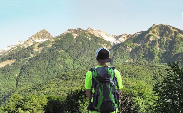 晴れた夏の日に山脈の背景に立っている若いアクティブな男の背面図。トレッキングでバックパックを持っている人