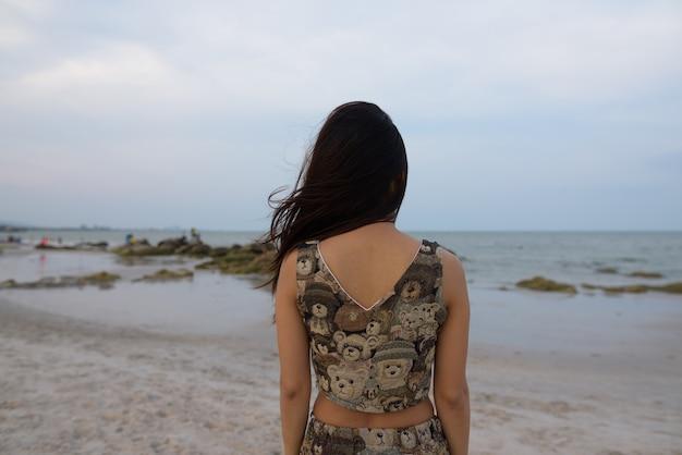 Вид сзади молодой азиатской женщины, смотрящей на живописный вид на паб