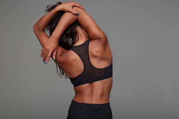 검은 스포티 한 상단에 포즈를 취하는 동안 그녀의 손을 스트레칭 젊은 운동 어두운 피부 곱슬 갈색 머리 여성의 다시보기. 피트니스 여성 모델