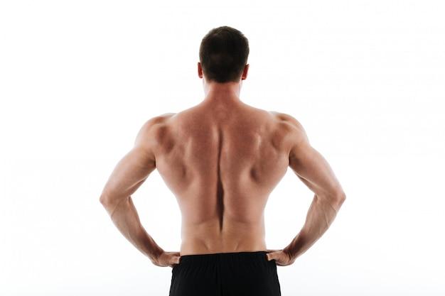 彼の腰に手で立っている若い運動スポーツ男の背面図
