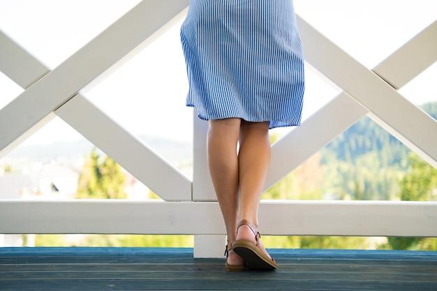 自然の景色を楽しむバルコニーで若い美しい女性の背面図。新鮮な空気で休むという概念。