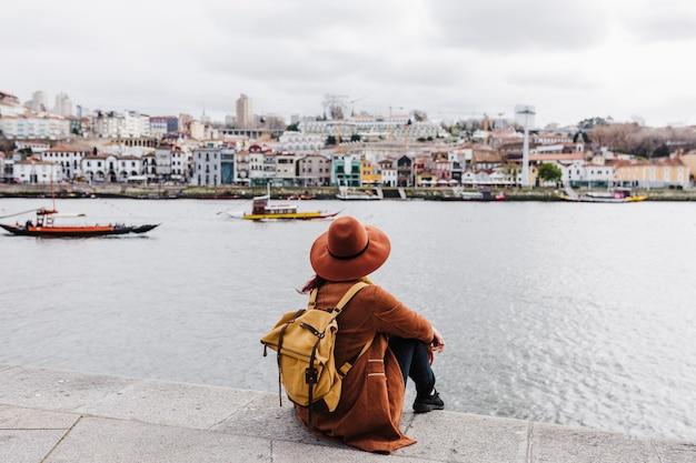 Вид сзади молодой красивой женщины, сидящей у реки на закате, наслаждаясь видами порту. концепция путешествия