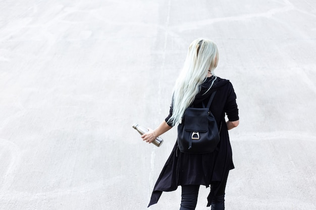 Вид сзади молодой блондинки, одетой в черное с рюкзаком, держа в руке стальную термо-бутылку.