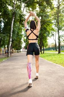 Вид сзади молодой женщины bruette, нагревающейся на открытом воздухе. вид в полный рост неузнаваемой подходящей девушки в черной спортивной одежде, тренирующейся в летнем парке, с кинезиологическими эластичными красочными лентами.