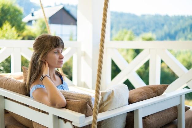 여름 자연의 전망을 즐길 수 있는 부드러운 베개와 함께 테라스 소파에서 쉬고 있는 젊은 브루네트 여성의 뒷모습. 신선한 공기에 자유 시간의 개념입니다.