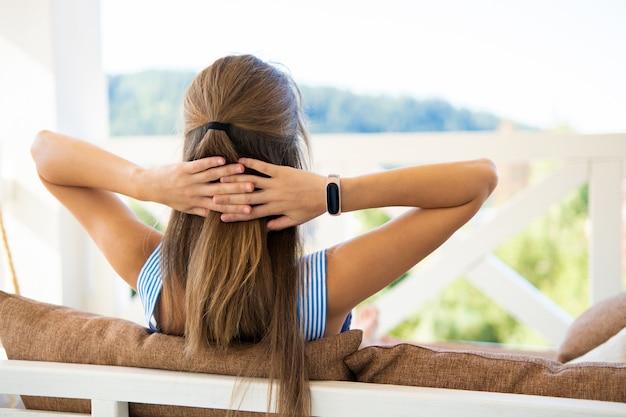 夏の自然の景色を楽しむ柔らかい枕とテラスのソファで休んでいる若いブルネットの女性の背面図
