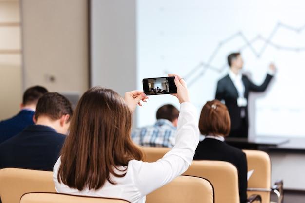 Вид сзади молодой бизнес-леди, снимающей видео с мобильного телефона на бизнес-конференции в зале заседаний