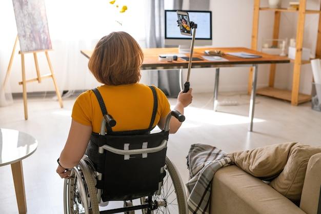 Вид сзади молодой современной женщины-инвалида в инвалидной коляске, перемещающейся по новому дому или квартире со смартфоном на палке