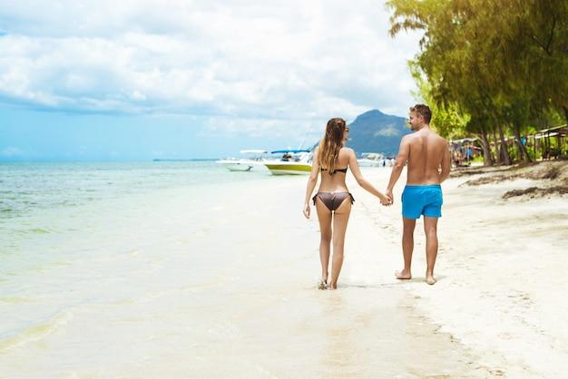 Вид сзади молодой пары в купальниках, взявшись за руки