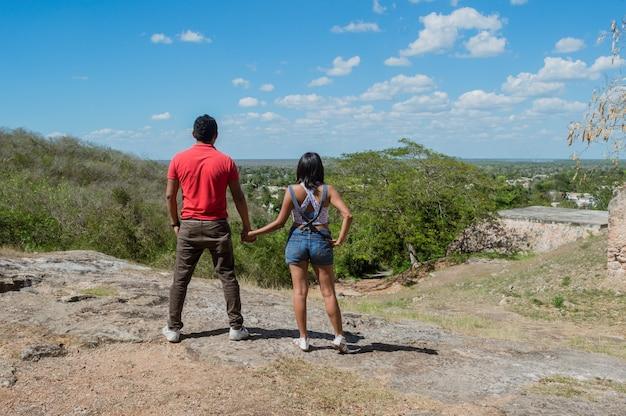 Вид сзади молодой пары, смотрящей на горизонт с высоты холма