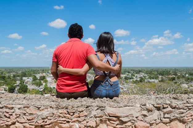 Вид сзади молодой пары, глядя на окраину города с высоты в эрмита-де-текакс