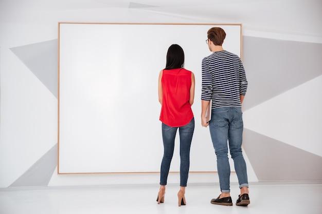 空の空白のボードを見ている展示会の若いカップルの背面図。フルレングスの画像