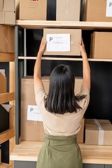 送信する前に木製の棚からクライアントの注文でパックされた段ボール箱を取る暗い長い髪の若い女性マネージャーの背面図