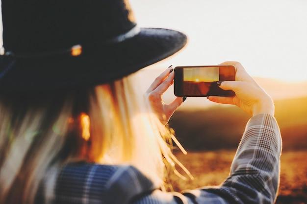 멋진 시골에서 석양의 사진을 찍기 위해 스마트 폰을 사용하는 젊은 여성의 뒷모습. 일몰 사진을 찍는 익명의 여자