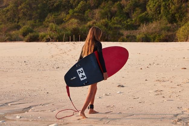 若いフィットの女の子の背面図は、痕跡を残して砂の上を歩きます