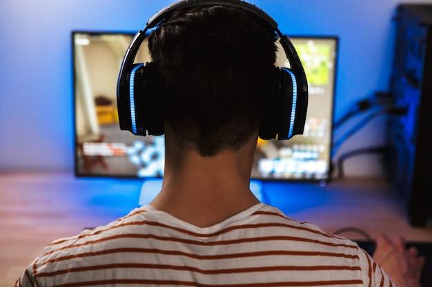 Вид сзади молодого геймера, играющего в видеоигры на компьютере
