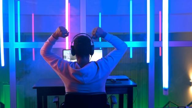 オンラインゲームに勝つ若いゲーマーの背面図。彼はネオンルームの自分のパソコンで遊んでいます。