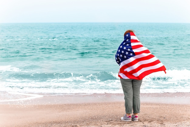 アメリカの国旗を持つ少女の背面図は海を見ています。