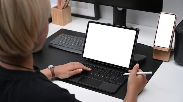 スタイラスペンを保持し、クリエイティブオフィスでコンピューターのテーブルで作業している若いグラフィックデザイナーの背面図。