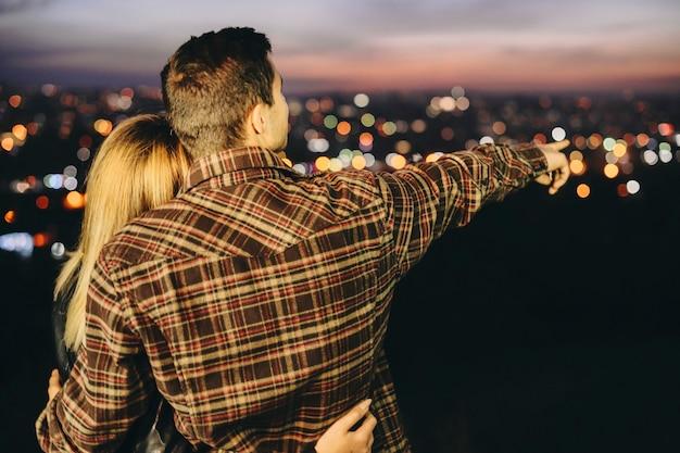 여자 친구를 포옹 하 고 밤 도시의 흐린 배경에 서있는 동안 거리에서 가리키는 체크 무늬 셔츠에 젊은 남자의 다시보기