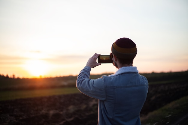 젊은 남자의 뒷모습은 스마트 폰으로 일몰 사진을 찍습니다.
