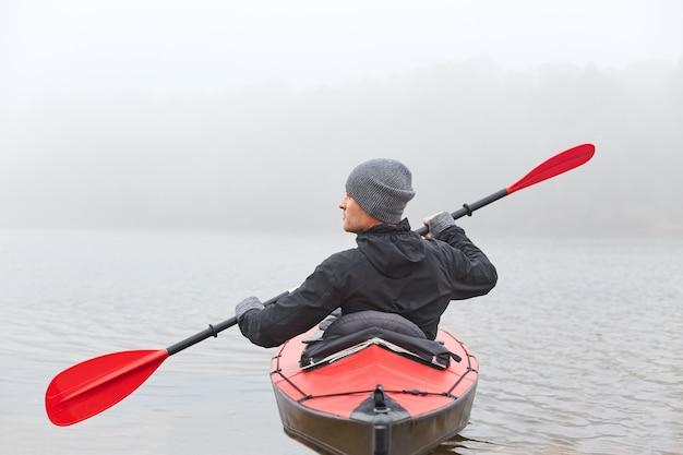 Вид сзади молодой красавец, каякинг в реке, проводит туманное утро в каноэ