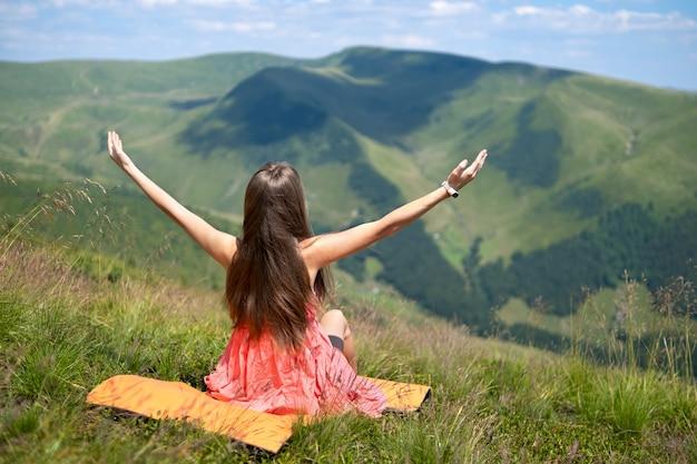 바람이 부는 날 여름 산에서 풀이 무성한 언덕에 앉아 빨간 드레스를 입은 젊은 행복한 여성 여행자의 뒷모습이 팔을 쭉 뻗고 자연 경관을 즐기고 있습니다.