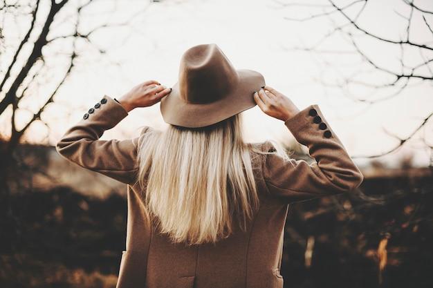 秋の田園地帯のぼやけた背景に立っている間、帽子に触れるエレガントなジャケットの若い女性の背面図。自然の中で帽子に触れるエレガントな女性