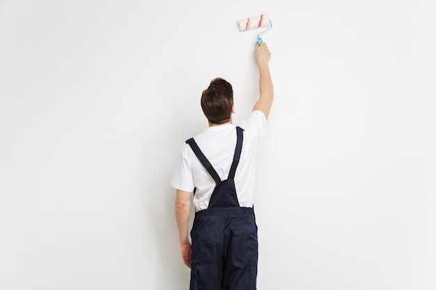 Вид сзади молодого мужчины-строителя, рисующего стену с краской на серой стене