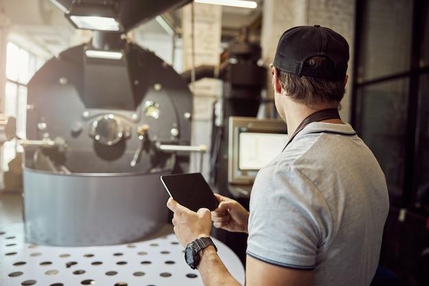 전문 커피 로스팅 장비의 작동 제어판을 보면서 태블릿 컴퓨터를 들고 젊은 남자의 다시보기