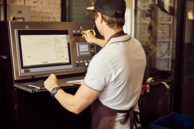 전문 커피 로스팅 장비의 제어판 작동 제어판에서 젊은 남자의 다시보기