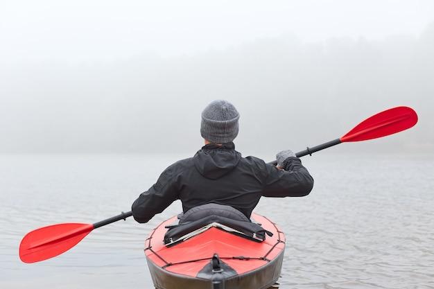 Вид сзади молодого человека каякинг на озере или вездеход в лодке, используя красно-черное весло,