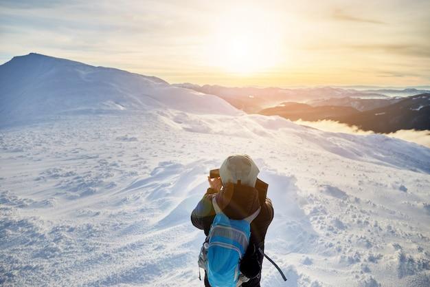 겨울 산의 사진을 만드는 젊은 남자의 뒷면