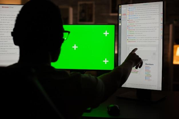 暗い部屋でゲームをプレイしながらコンピューターのモニターを指している若い男の背面図。緑色の画面で監視します。