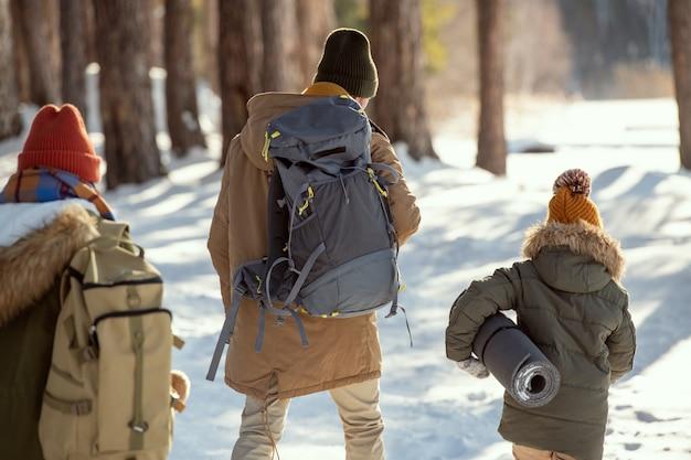 バックパックを持った若い男性とカントリーハウスに向かって移動するロールマットを持った少女、彼らに続くリュックサックを持った女性の背面図