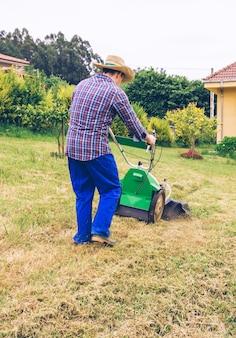麦わら帽子と芝刈り機で芝生を刈る格子縞のシャツを持つ若い男の背面図