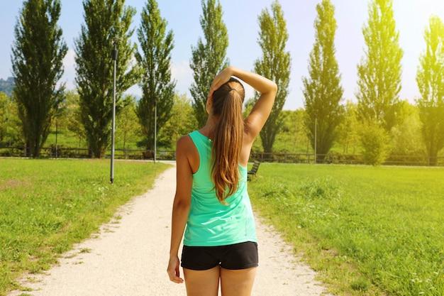 公園で首を伸ばして若いランナー女性の背面図です。