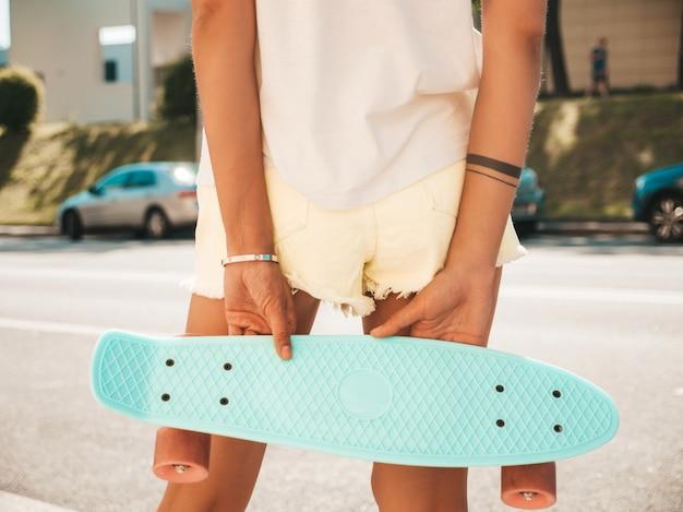 ショートパンツで若いセクシーな女性のお尻の背面図。通りでポーズをとって青いペニースケートボードを持つ少女