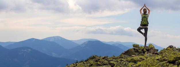 明るい青い朝の空と霧深い山々の背景に岩が多い上にヨガのポーズで片足でバックパック立って若いスリムな観光女の子の背面図。観光、旅行、登山のコンセプトです。