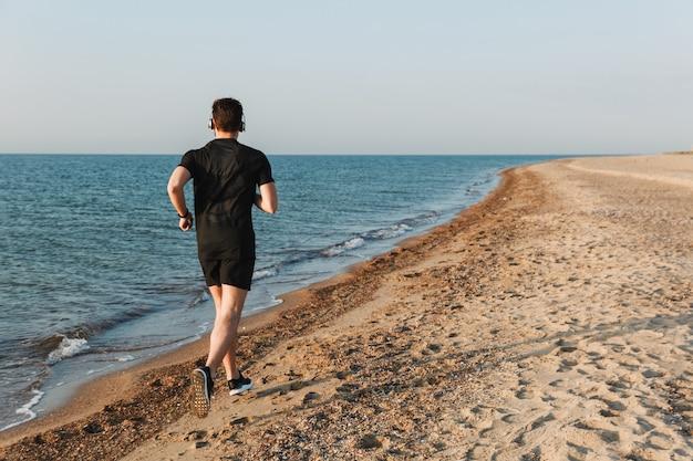 ビーチで実行されている若いスポーツマンの背面図