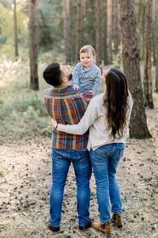 若いスタイリッシュな両親、父と母、彼らの小さな男の子を抱いて、カメラに微笑んでいる背面図。屋外の家族の肖像画